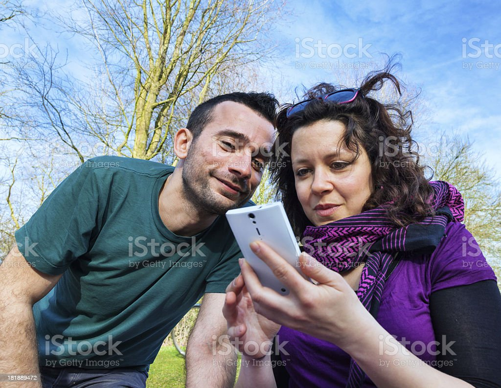 Happy young couple looking at a smart phone royalty-free stock photo