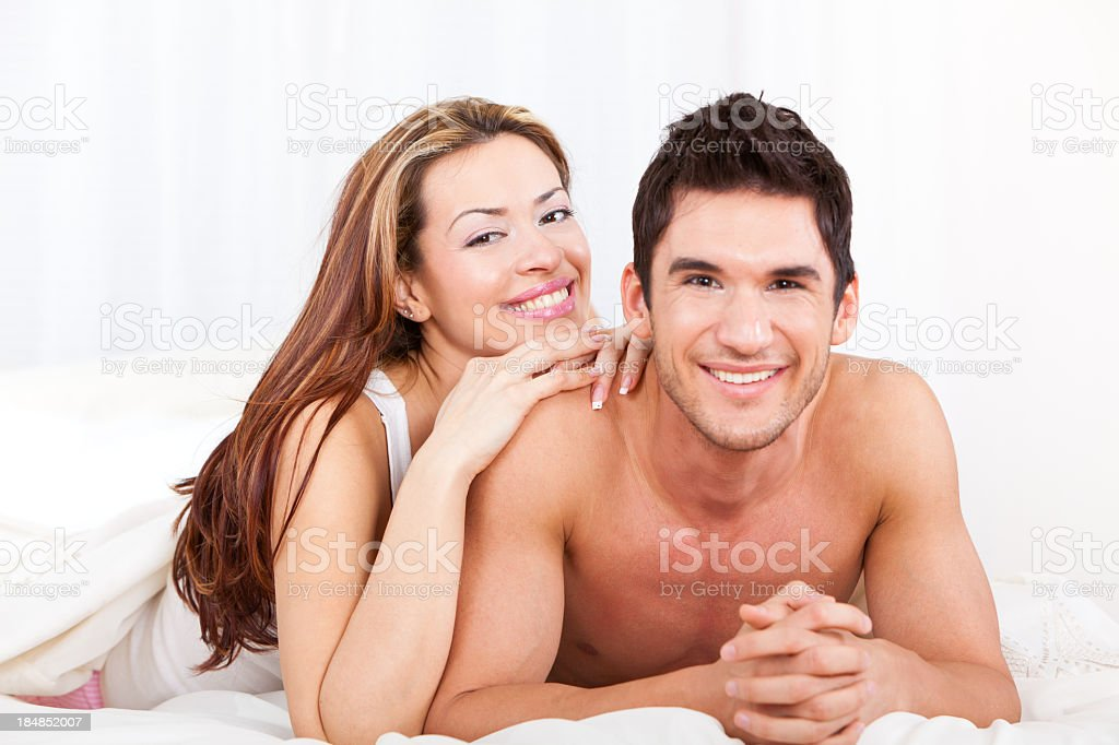 Happy young couple lying down in bed royalty-free stock photo