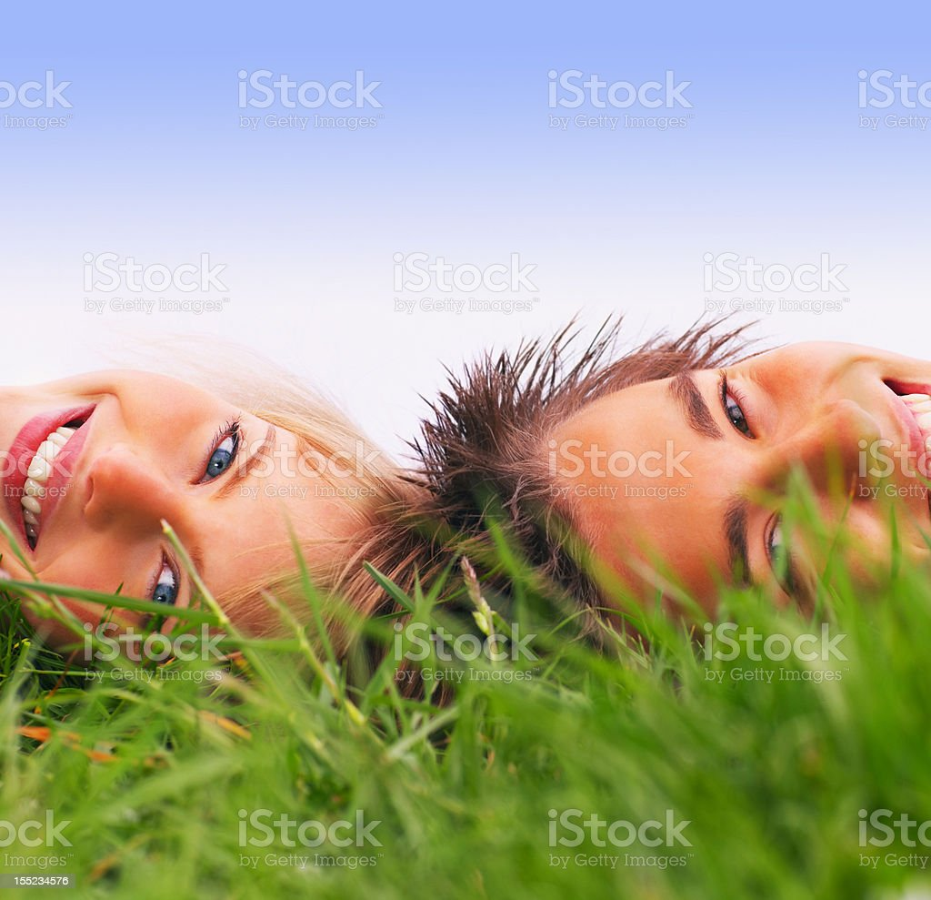 Happy young couple lying on grass royalty-free stock photo
