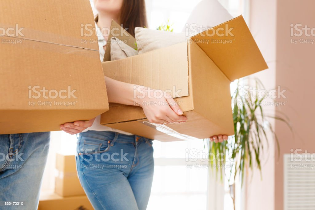 Happy young couple moving into new apartment with packaging boxes....