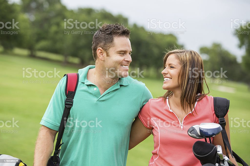 Happy young couple playing golf together on course stock photo