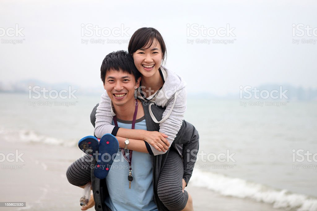 Happy Young Couple Playing On Beach - XLarge royalty-free stock photo