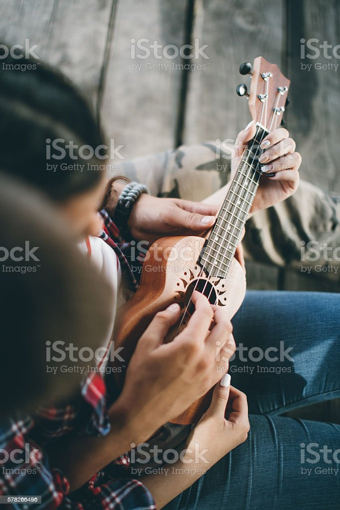 Happy young couple playing ukelele stock photo