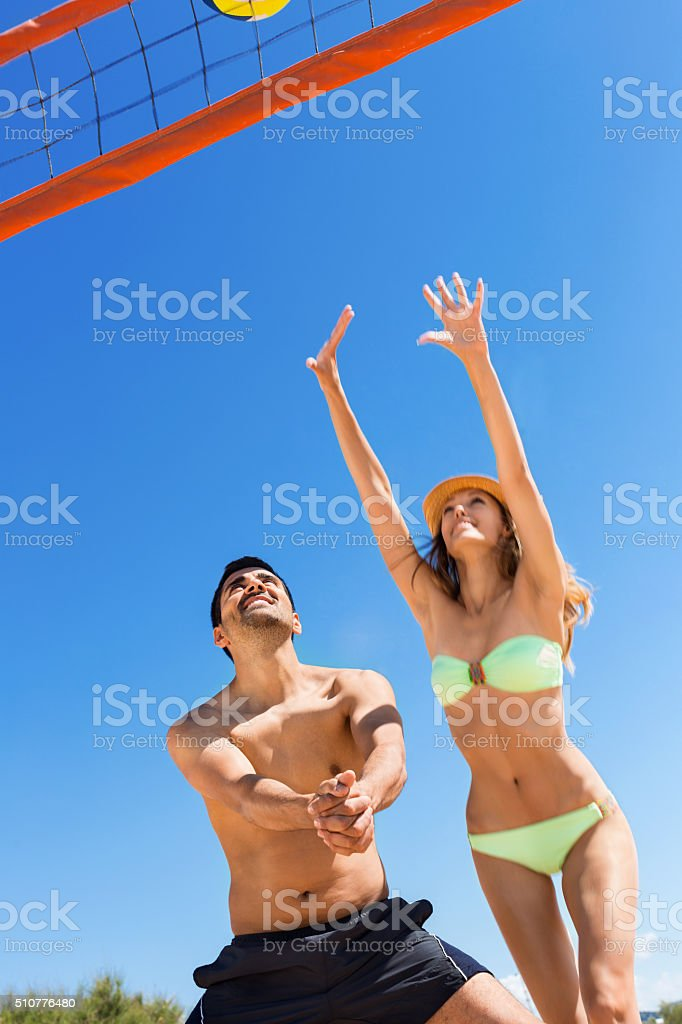 Happy young  couple playing volleyball stock photo