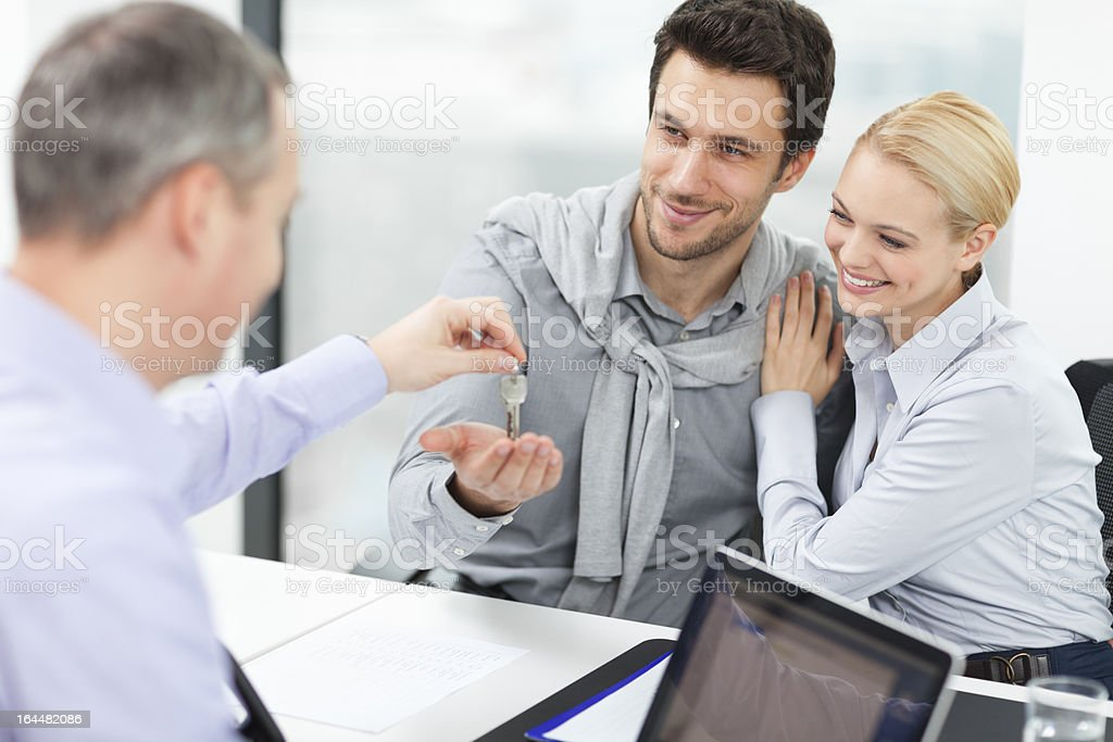Happy young couple receiving new home keys royalty-free stock photo
