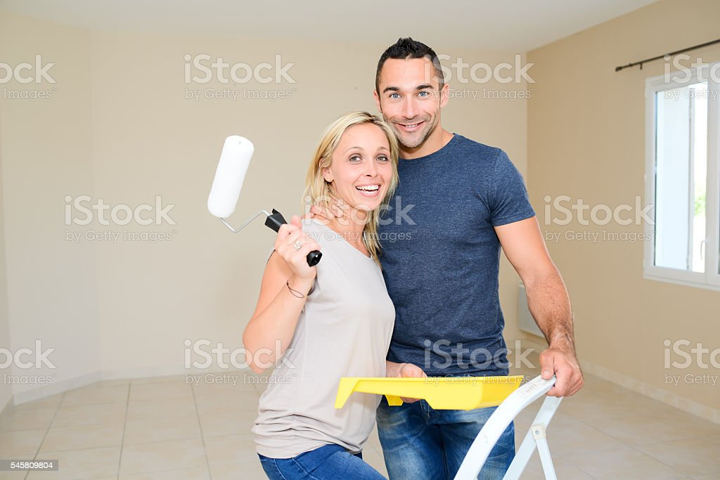 happy young couple renovating painting and moving into new house stock photo