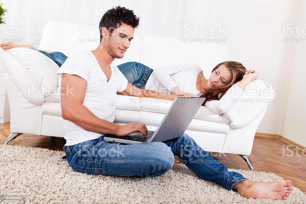 Happy young couple shopping from home stock photo