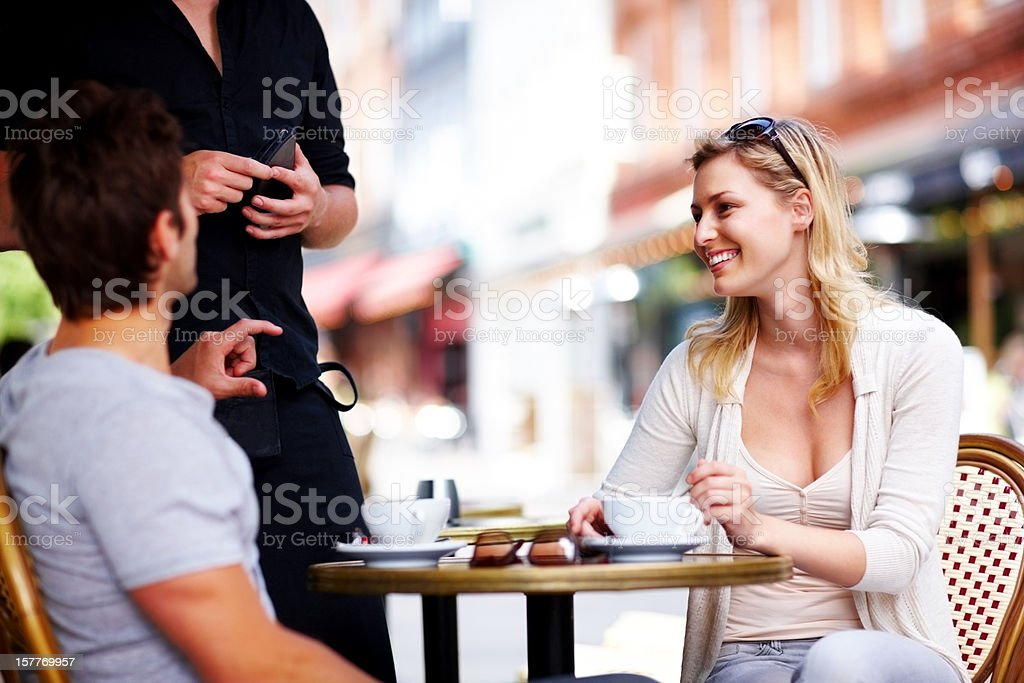 Happy young couple sitting at an open cafe royalty-free stock photo