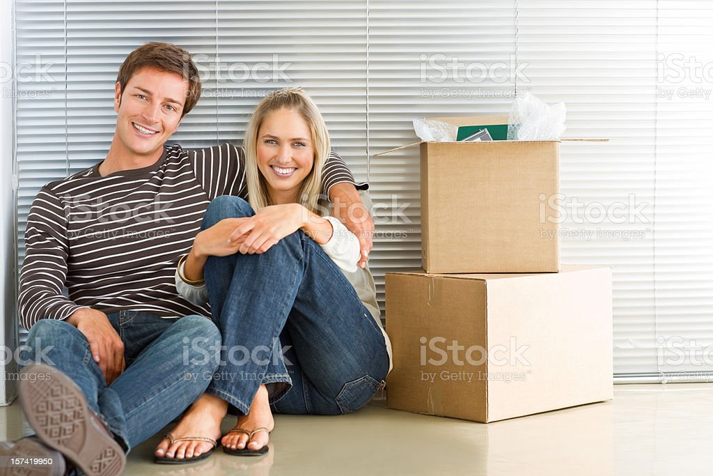Happy young couple sitting by boxes royalty-free stock photo
