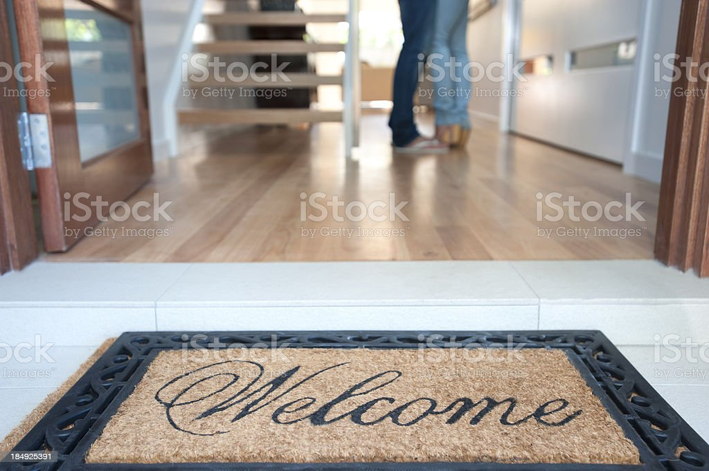 Happy young couple standing inside their new house stock photo