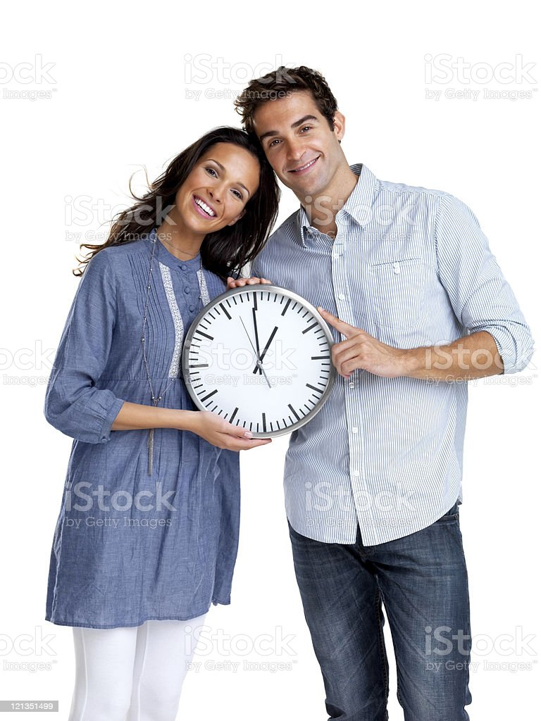 Happy young couple standing together with a clock stock photo