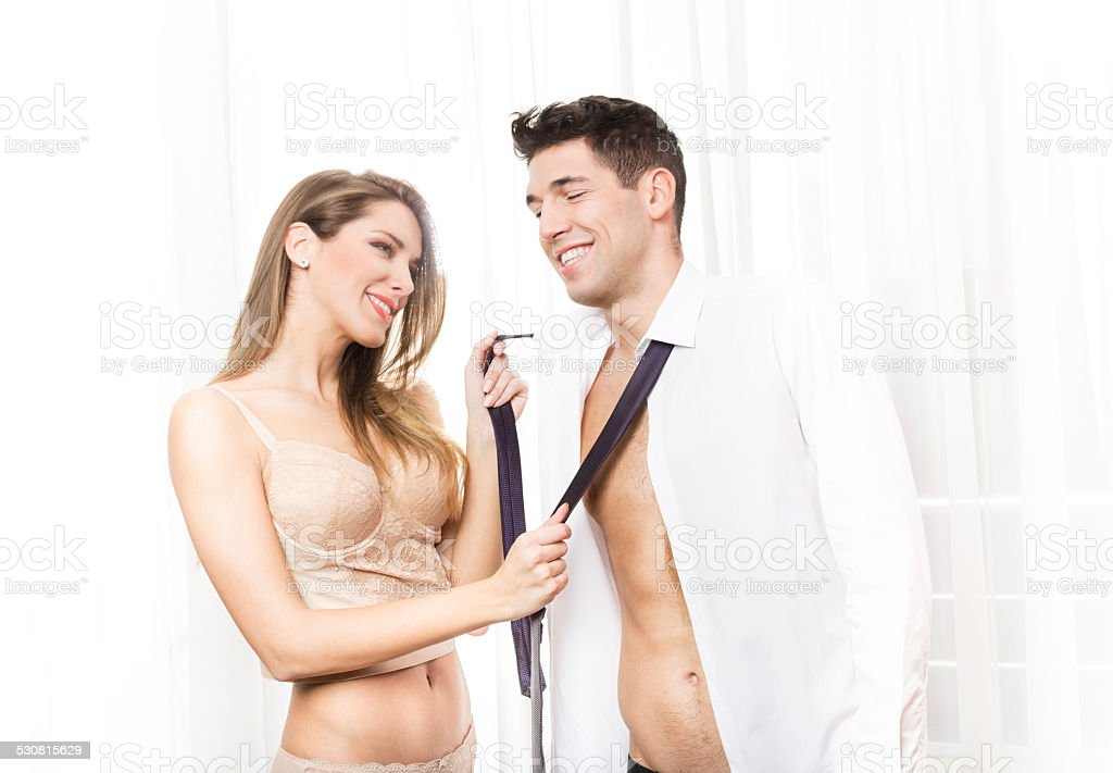 Happy young couple taking their clothes off stock photo