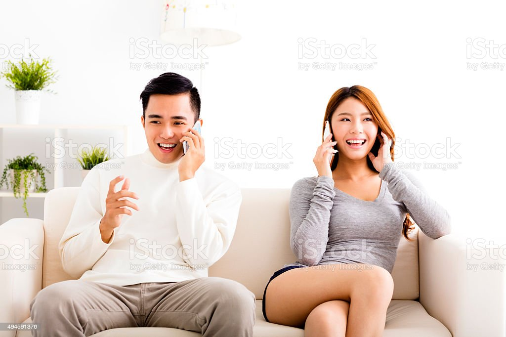 happy young  couple talking on the phones stock photo