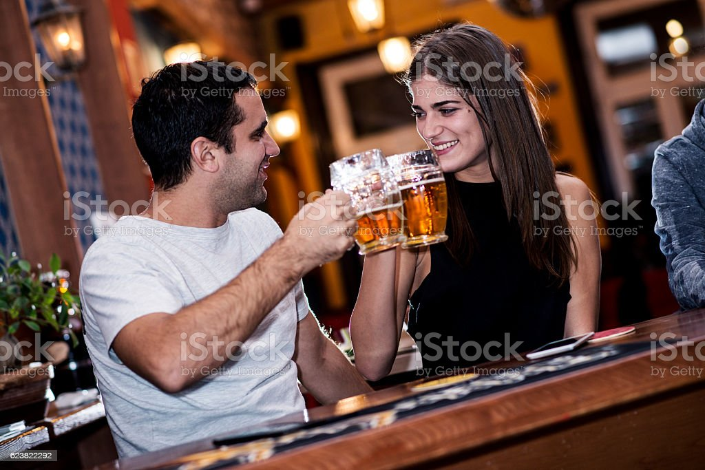 Happy young couple toasting with beer in a bar. stock photo