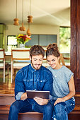 Happy young couple using digital tablet while sitting on step
