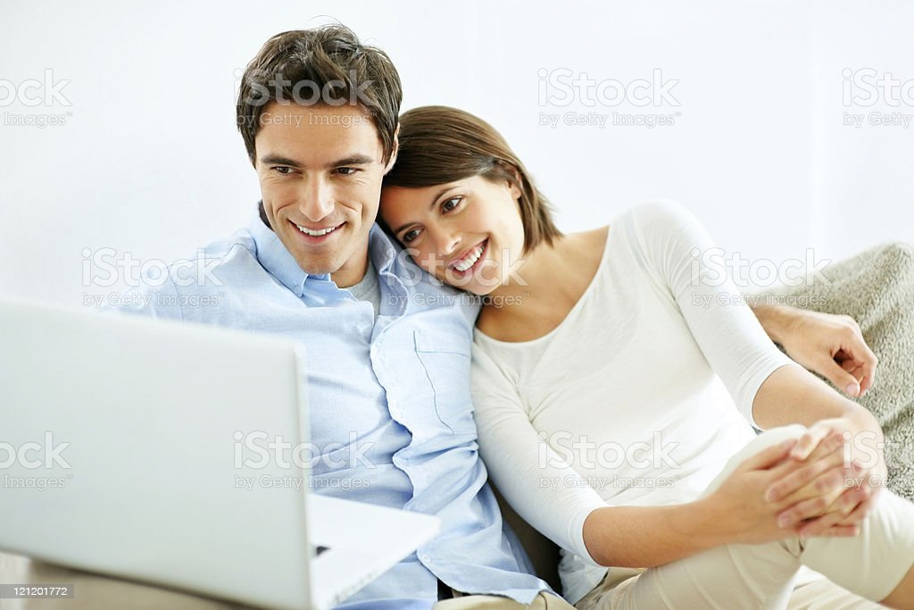 Happy young couple using laptop at home royalty-free stock photo