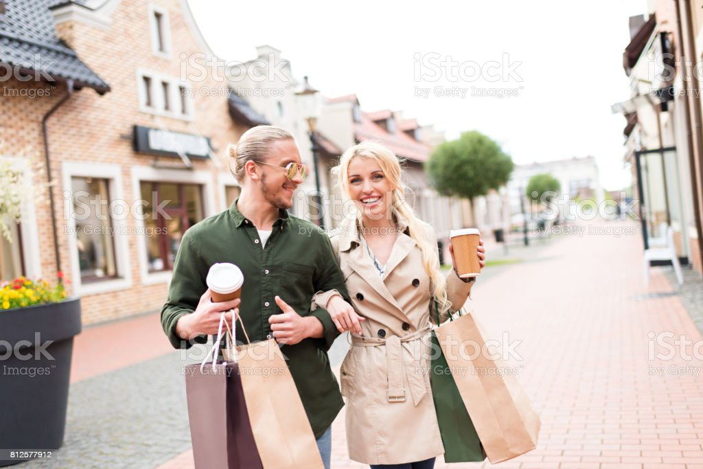 happy young couple walking and drinking coffee with shopping bags on the street stock photo