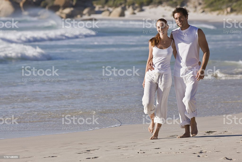 Happy young couple walking together on beach royalty-free stock photo