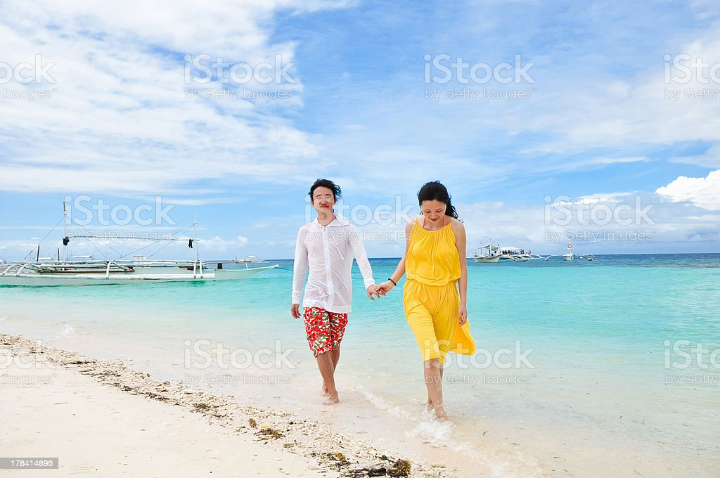 happy young couple walks in shallow water on tropical beach royalty-free stock photo