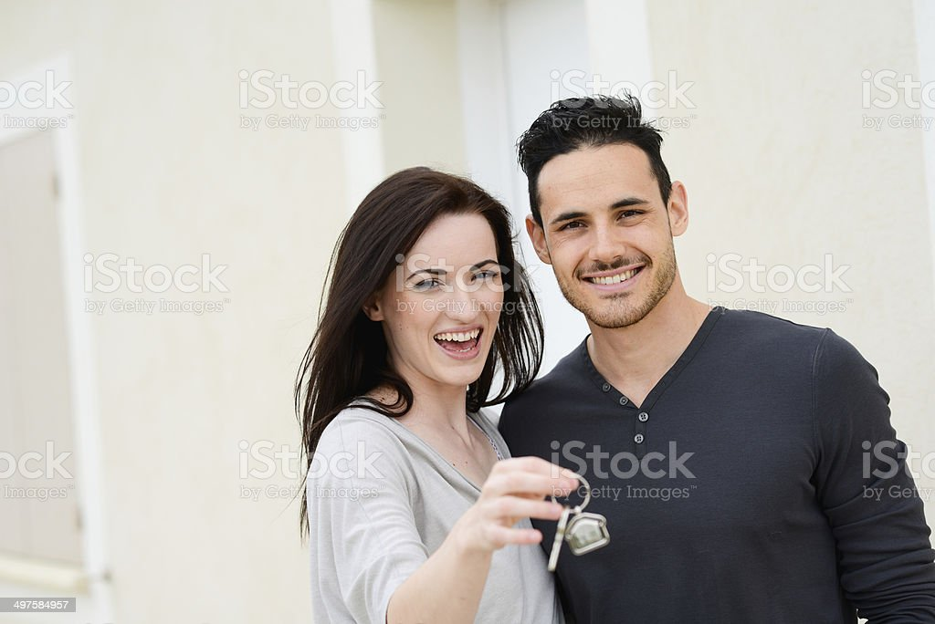 happy young couple welcome in new house showing door keys stock photo