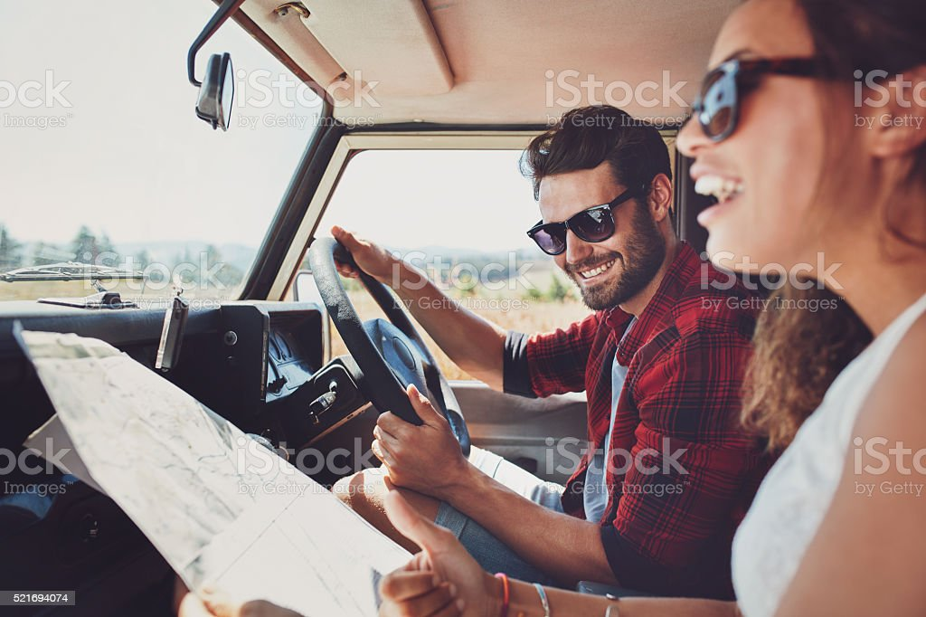 Happy young couple with a map in the car stock photo
