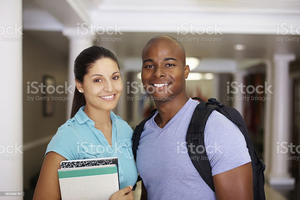 Happy young couple with bagpacks standing in a campus corridor royalty-free stock photo