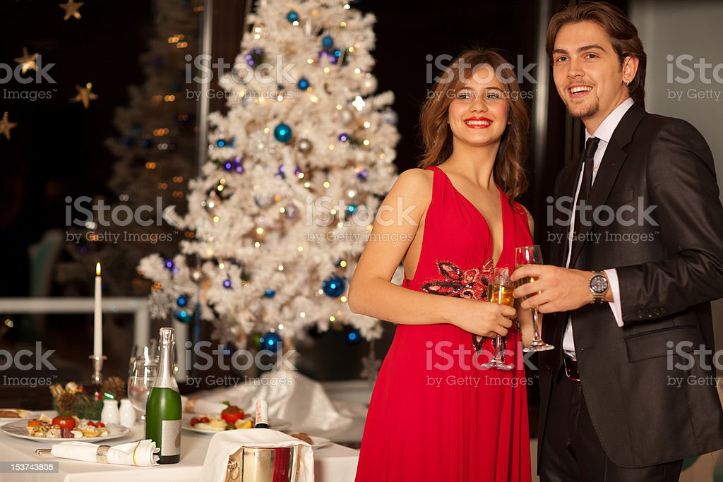Happy young couple with champagne glasses at christmas royalty-free stock photo
