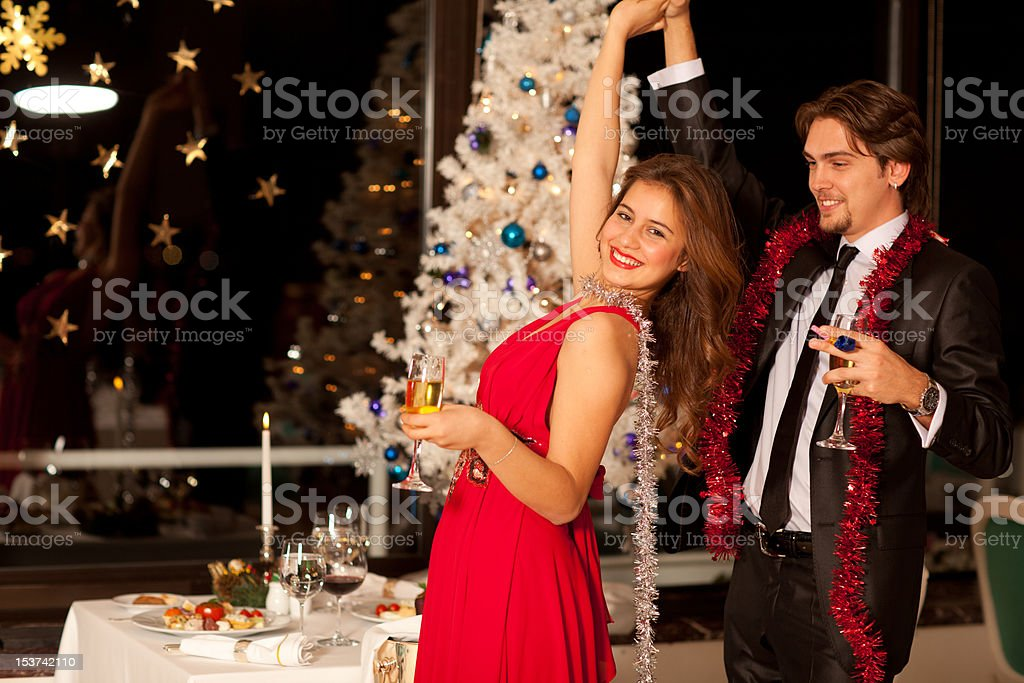 Happy young couple with champagne glasses dancing at christmas stock photo