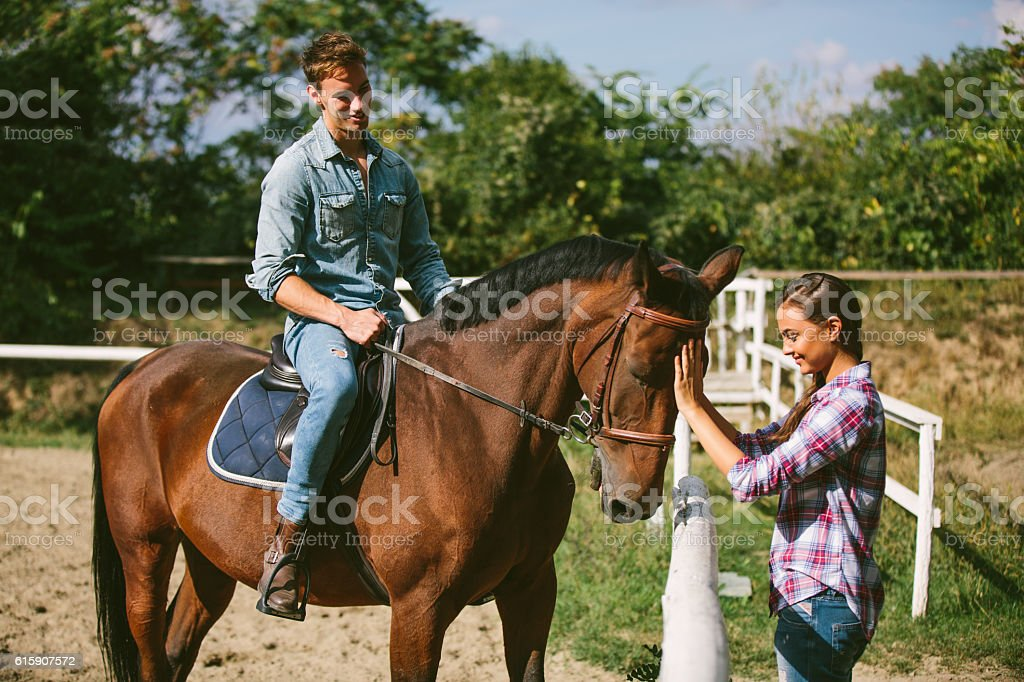 Happy young couple with horse outdoors. stock photo