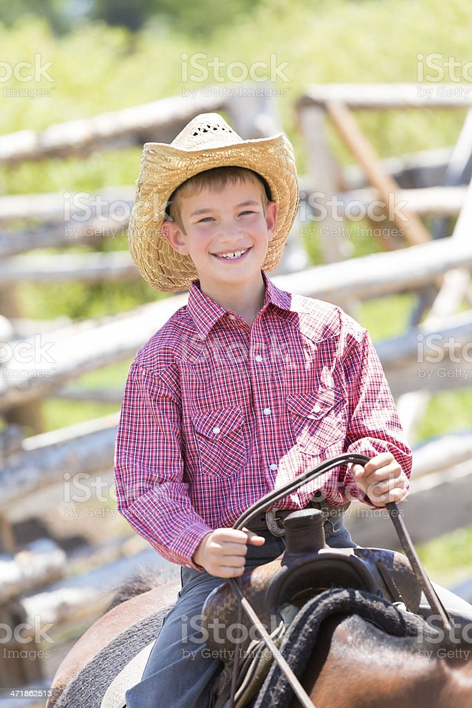 Happy young cowboy sitting in saddle on horse at ranch royalty-free stock photo