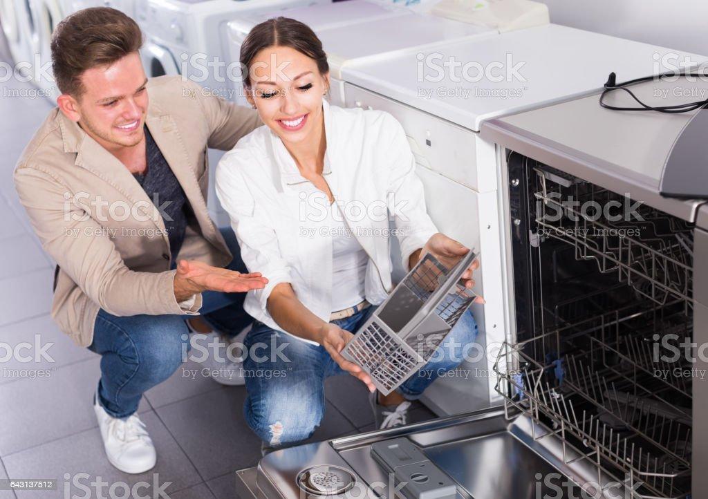 happy young customers choosing new dish washing machine stock photo