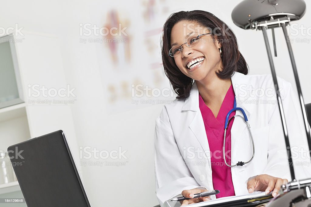 Happy Young Doctor in Her Office Smiling at Patient royalty-free stock photo