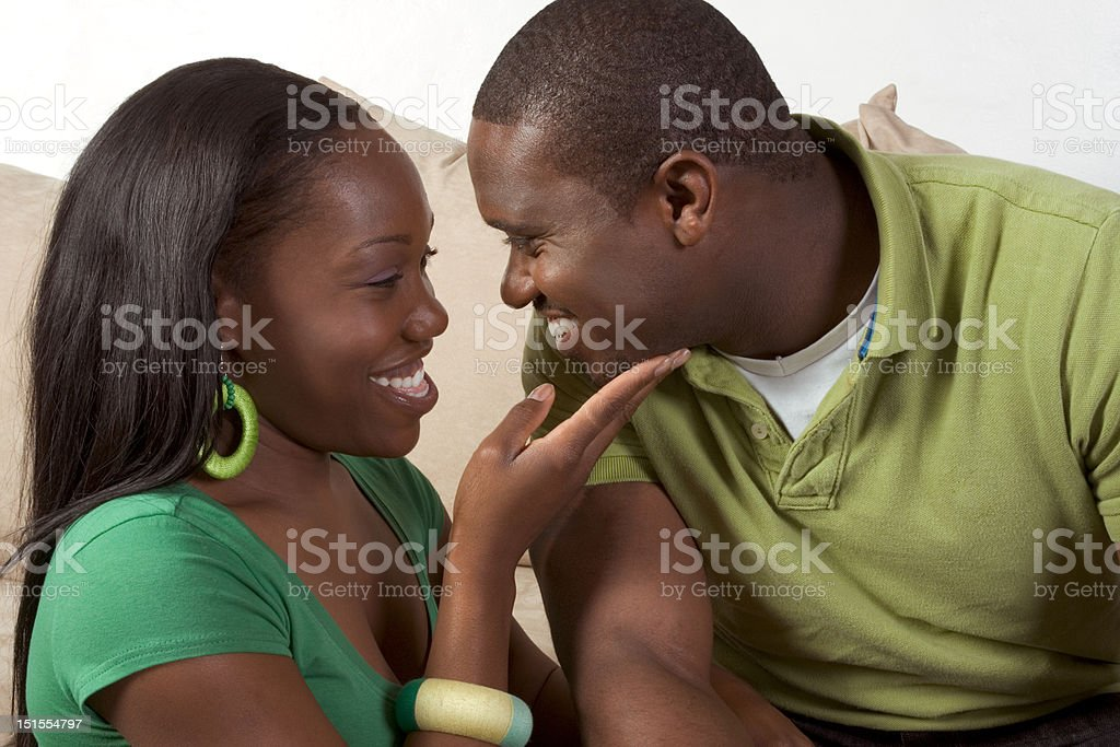 Happy young ethnic black couple sitting on couch stock photo