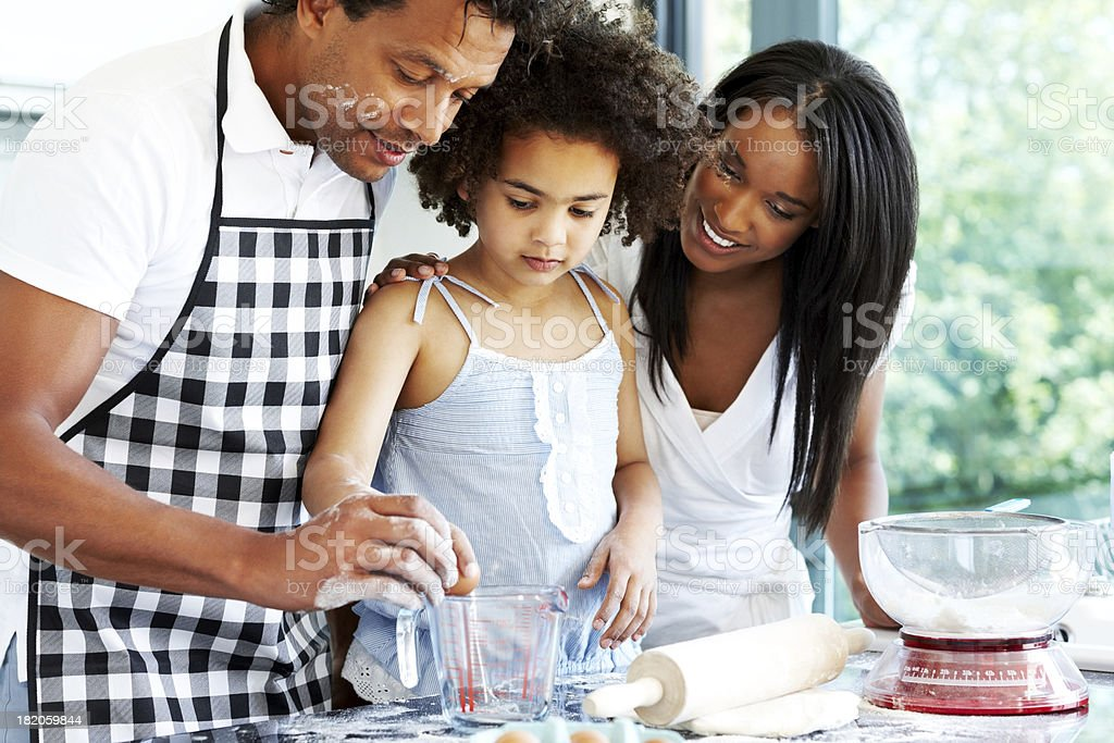Happy young family baking in kitchen royalty-free stock photo