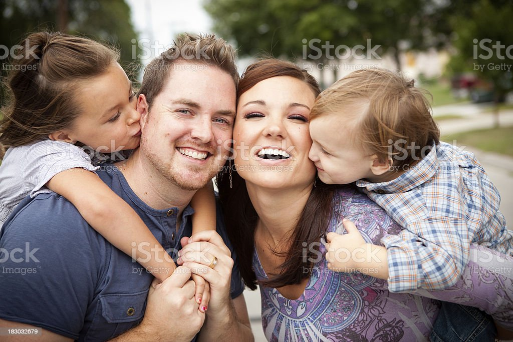 Happy Young Family Giving Kisses to Each Other Outside royalty-free stock photo