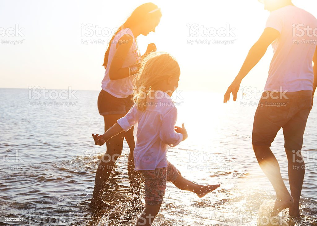 Happy young family having fun running on beach at sunset stock photo
