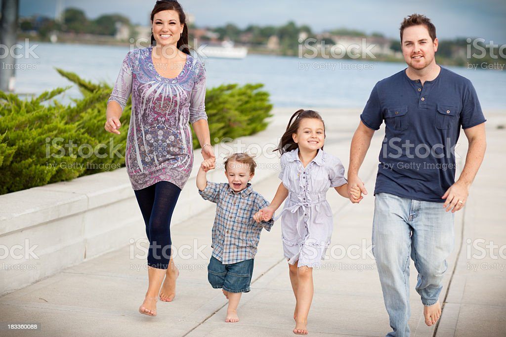 Happy Young Family Holding Hands While Walking Together Outside royalty-free stock photo