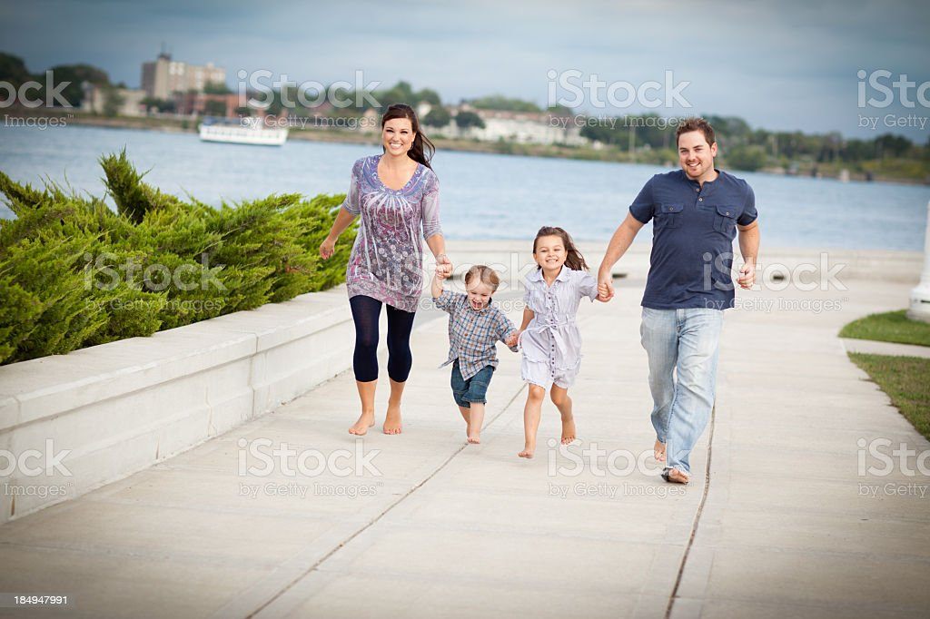 Happy, Young Family Holding Hands While Walking Together Outside royalty-free stock photo