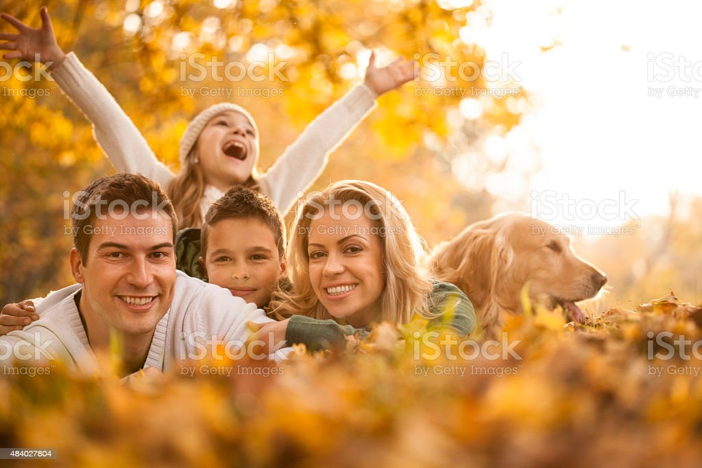 Happy young family in the autumn park with dog stock photo