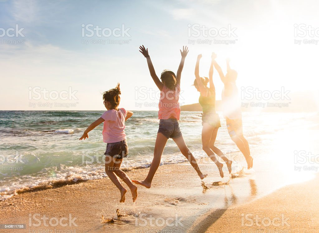 happy young family jumping on beach at sunset stock photo