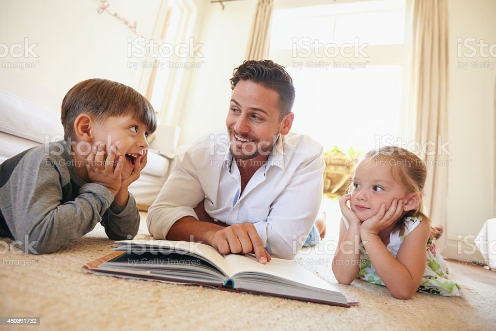 Happy young family lying on the floor reading a book stock photo