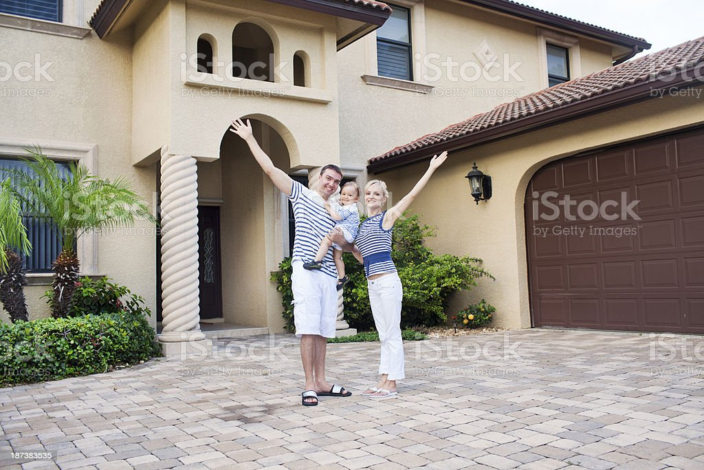 Happy young family next to their luxury home royalty-free stock photo