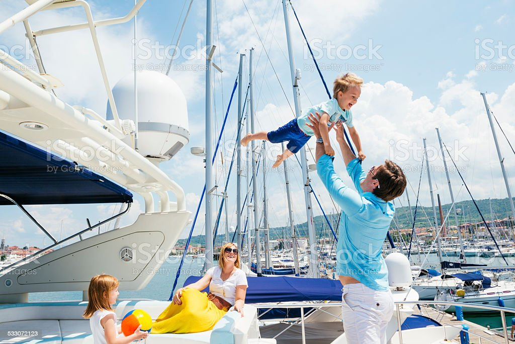 Happy young family on motor yacht stock photo