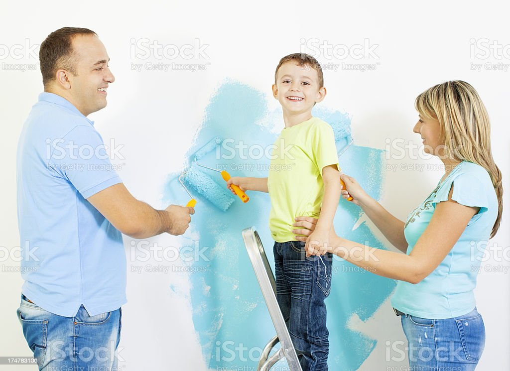 Happy Young Family Painting the wall. royalty-free stock photo