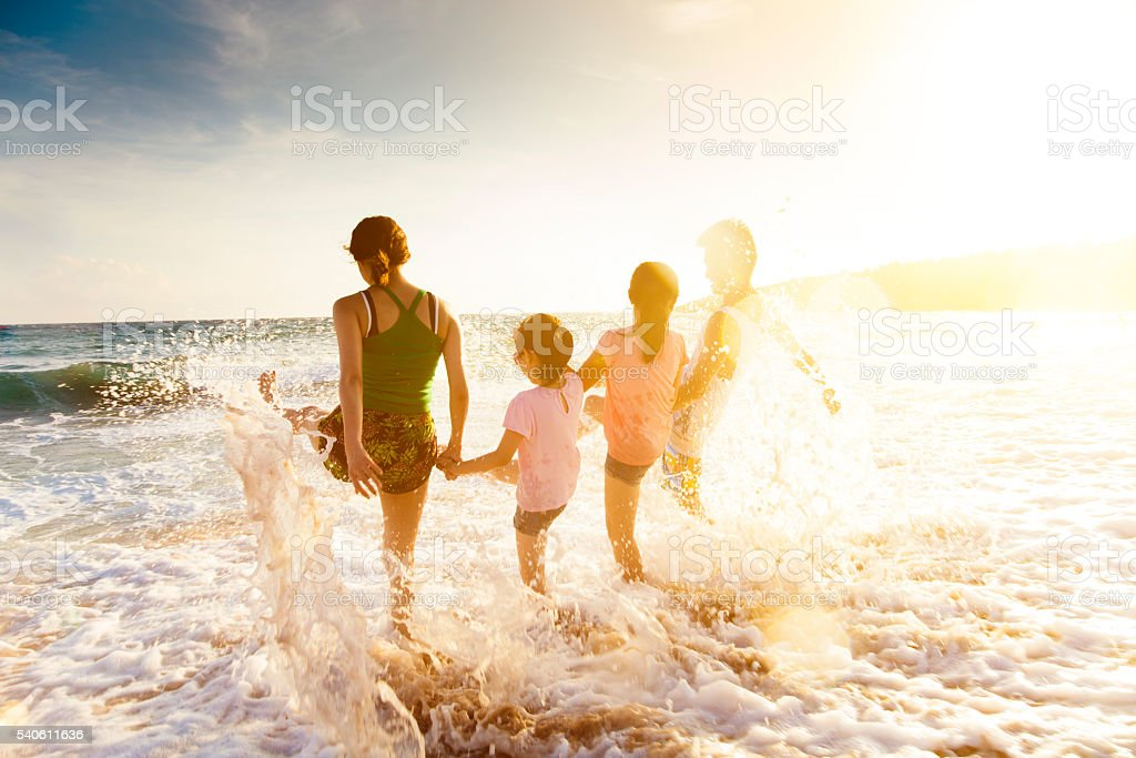 happy young family playing on beach at sunset stock photo