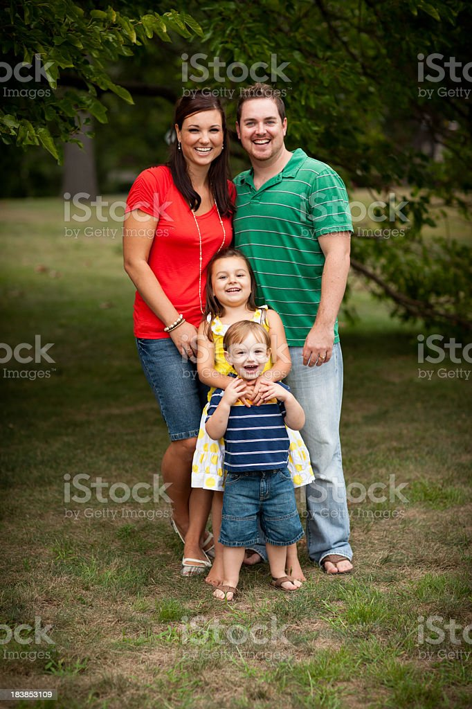 Happy Young Family Standing Together in Grass Outside royalty-free stock photo