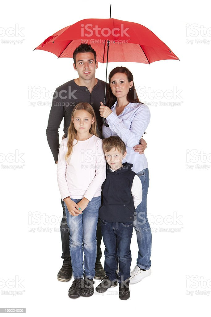 Happy young family standing under one umbrella stock photo