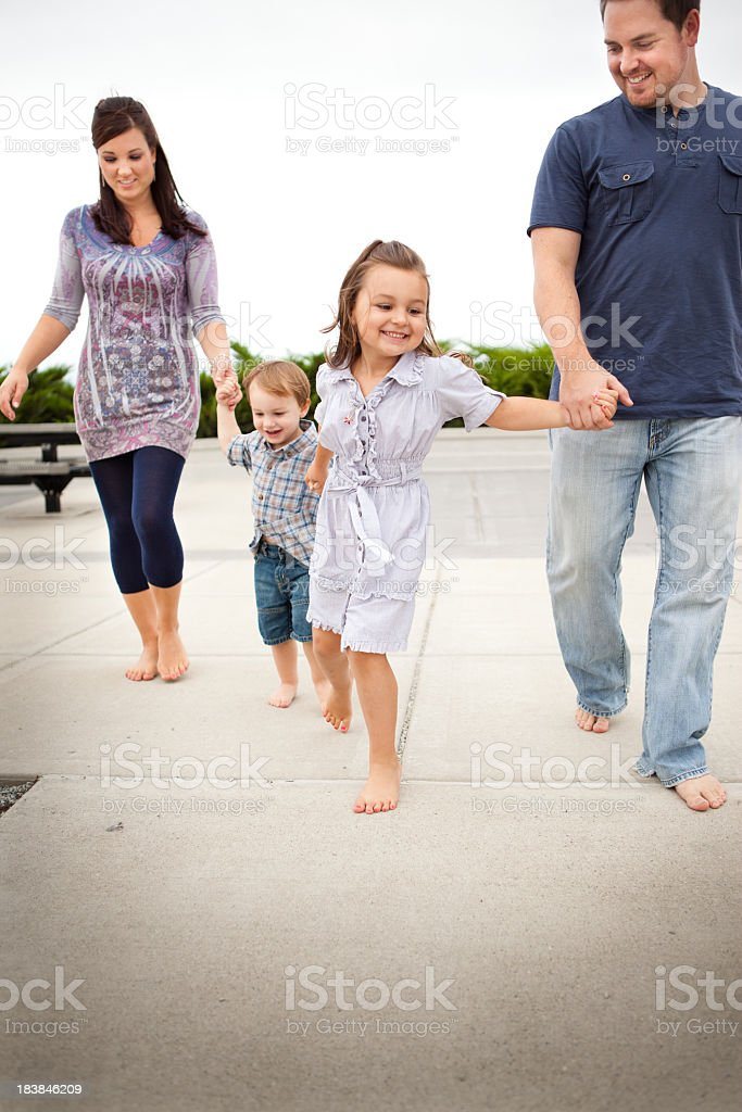 Happy Young Family Walking Together Outside royalty-free stock photo