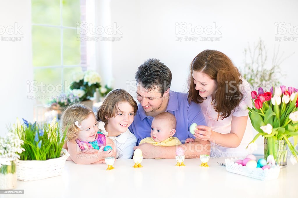 Happy young family with three children in sunny dining room stock photo