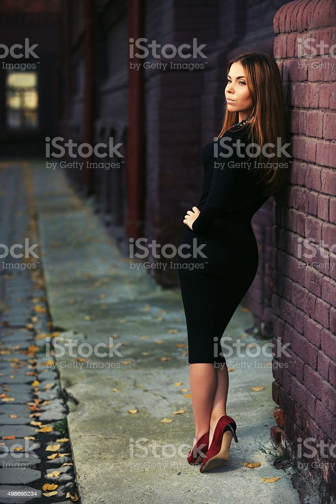 Happy young fashion woman in black dress stock photo